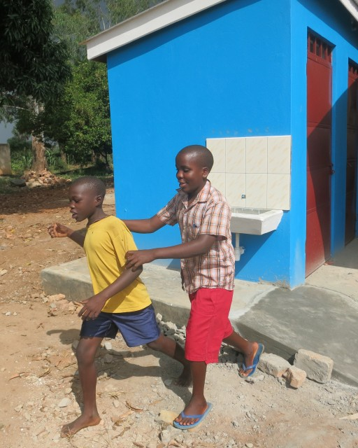 Two sight impaired children walk past the new toilets at the St Francis Madera School for the Blind