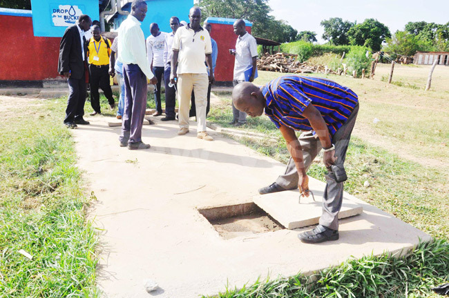 Water and sanitation officers examining a septic tank for the flush toilets of Hope Junior School in Soroti district.
