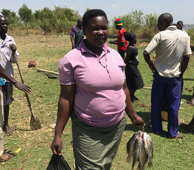 Betty buying fish at Lake Kyoga in Uganda. Betty is a member of the Fr Omoding Primary School village savings group, set up by Drop in the Bucket