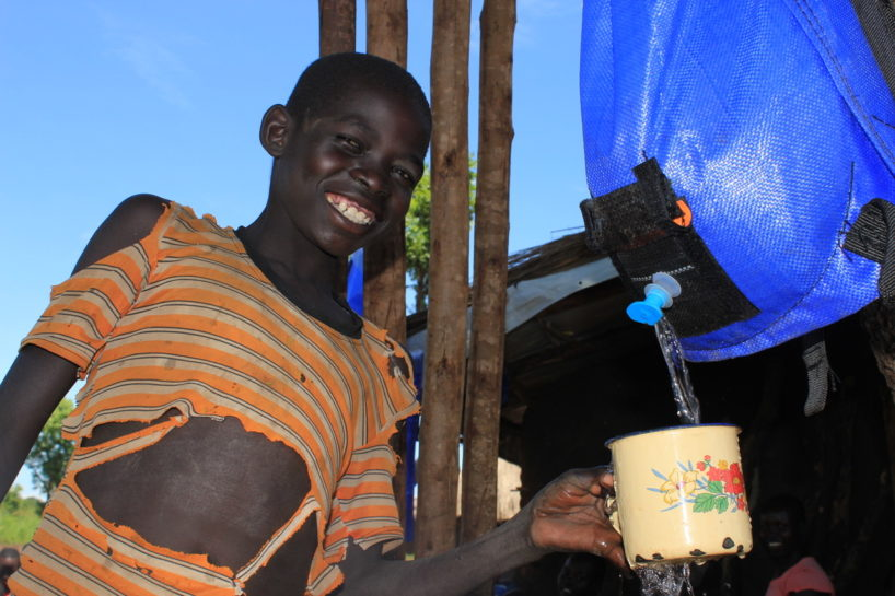 World Refugee Day - A South Sudanese refugee child getting clean water from a Pack H2O water backpack in Uganda