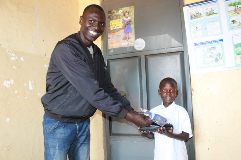 Drop in the Bucket Employee gifts a young student a new pair of shoes in Uganda