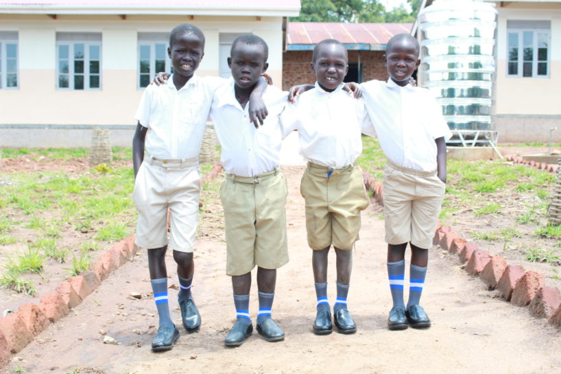 Four young boys at school in Uganda show of their new shoes
