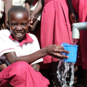 Girl drinking clean water from a new well drilled by Drop in the Bucket at the Busia Primary School in Koboko, Uganda.