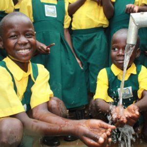 Two Happy Students In Uganda Smiling At Clean Water Well