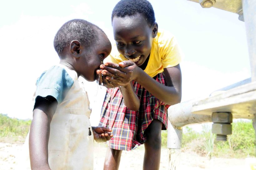 Older child in Uganda helps younger child take a sip of clean water