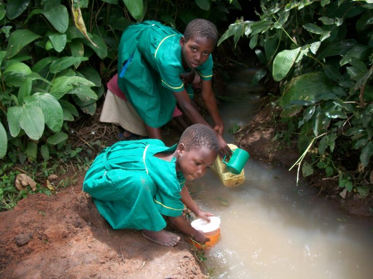 Two small girls fetch water from a dirty stream in Uganda