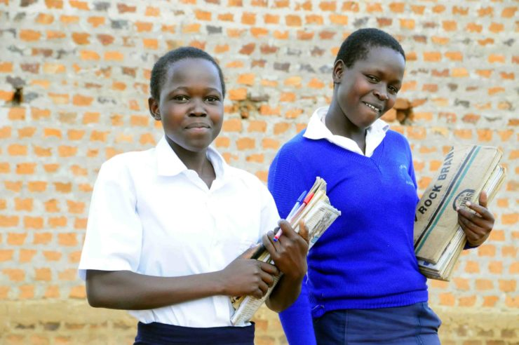 Two teenage female students with their books smiling in front of their school in Uganda