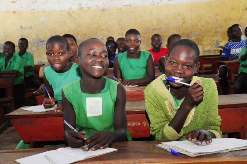 Students in Uganda smiling in class