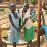 Two girls at a borehole well drilled by Drop in the Bucket for the Goan Quarters community in Gulu, Uganda.